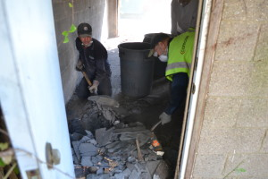 AL Chernov and Joe Divack picking up roof tiling in a garage in Beltzhoover. Photo by Tyler Polk.