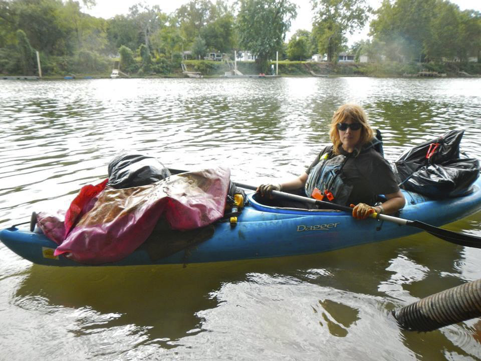 Melissa Rohm sits in her kayak filled with garbage she picked out of the river.