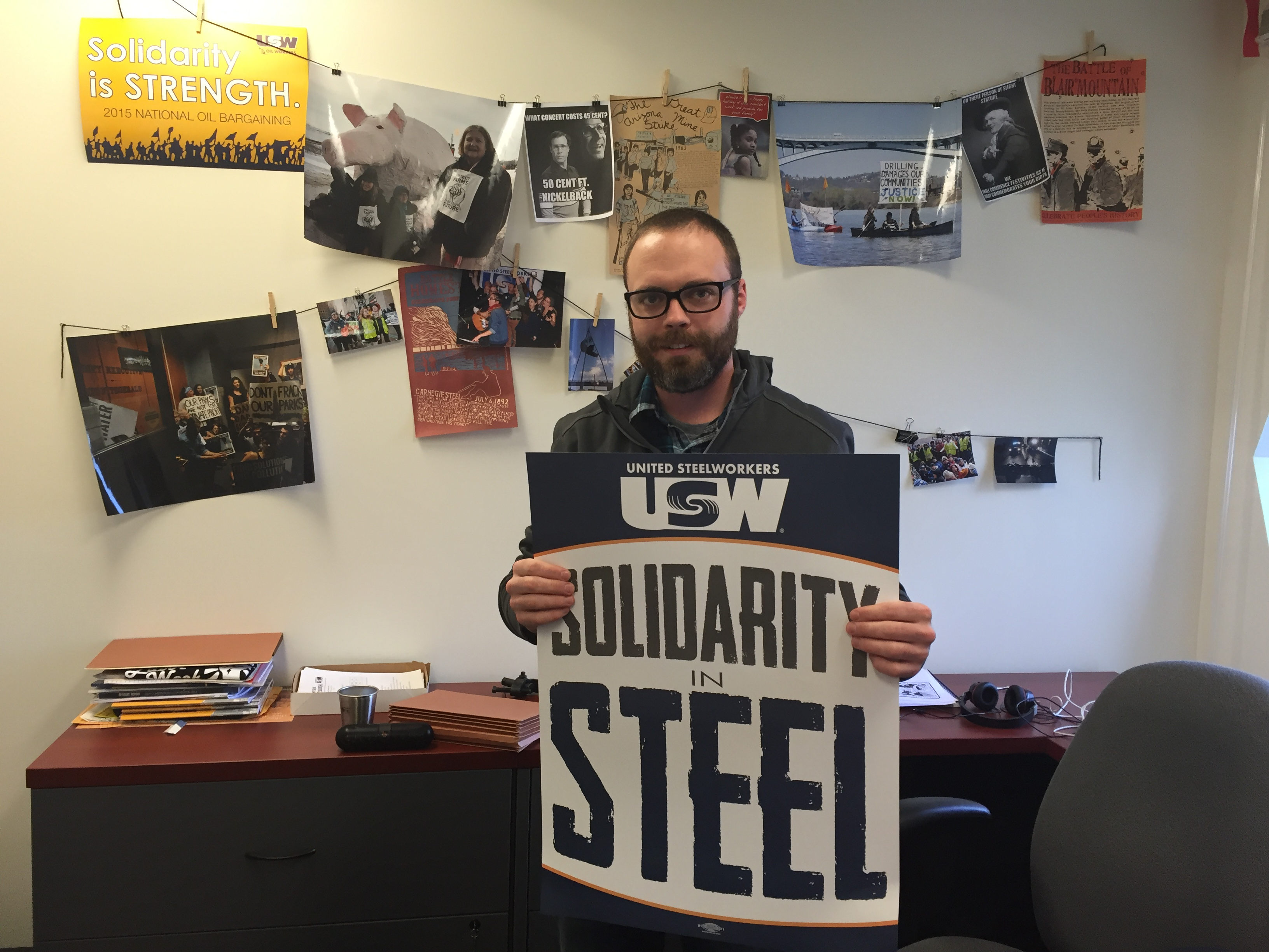 Patrick Young of the United Steelworkers holds a sign of solidarity in his office. Photograph: Alicia Green